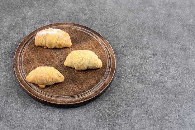 Holzbrett mit hausgemachten frischen keksen auf marmortisch.