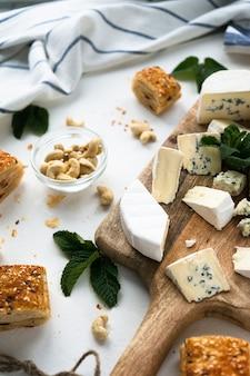 Holzbrett mit käse, auf einer hellen oberfläche