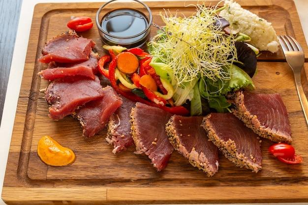 Holzbrett mit thunfisch-tataki und gekeimtem gemüse auf einem tisch