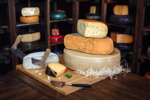 Holzbrett mit verschiedenen arten des köstlichen käses auf tabelle