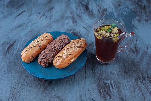 Holzbrett mit verschiedenen süßen eclairs und einer tasse tee auf marmoroberfläche.