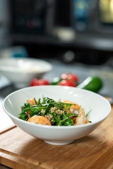 Holzbrett mit weißer keramikschale mit appetitlichem salat aus rucola, gekochten garnelen und anderen zutaten mit öl