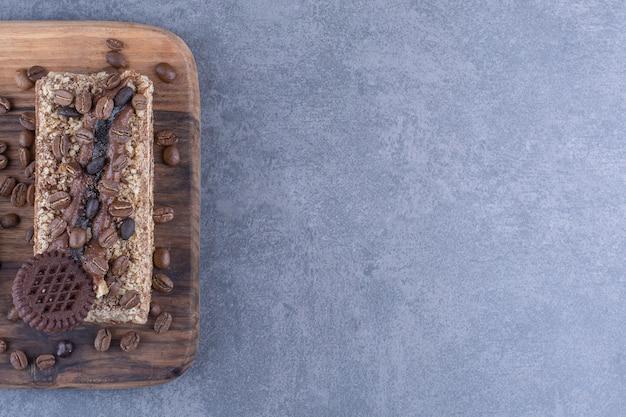 Holzbrett unter einem stück kuchen mit keks und kaffeebohnen auf marmoroberfläche