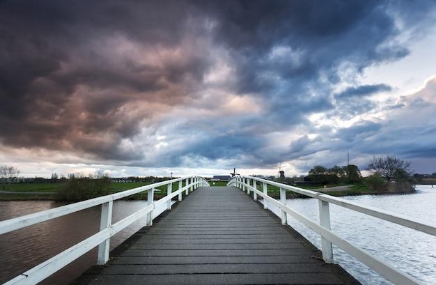 Holzbrücke auf dem hintergrund des drastischen bewölkten himmels