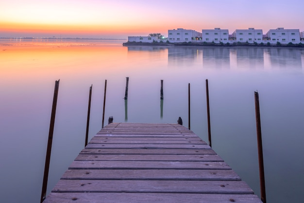 Holzbrücke heraus auf dem wasser über buntem himmel des sonnenaufgangs mit traditionellem lokalem haus im inselhintergrund, bahrain.