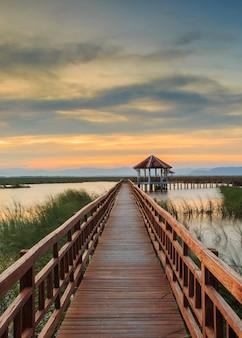 Holzbrücke im lotossee auf sonnenuntergangzeit bei khao sam roi yot national park, thailand