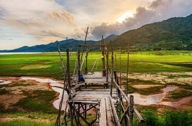Holzbrücke mit blick auf landschaft und fluss in der dämmerung