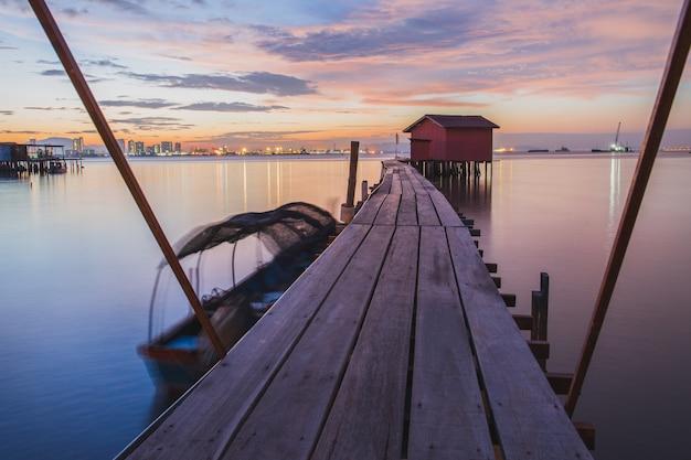 Holzbrücke mit hütte bei sonnenaufgang in chew steg georgetown penang island malaysia.
