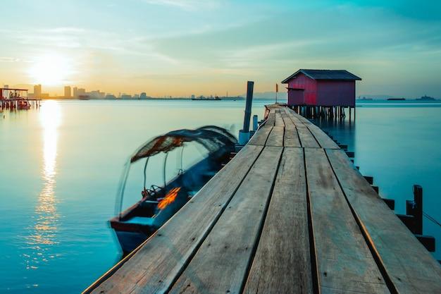 Holzbrücke mit hütte bei sonnenaufgang in chew steg georgetown penang malaysia.