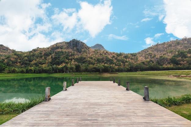 Holzbrücke oder steg mit berg und blauem himmel am see