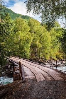 Holzbrücke über den fluss chuya, in der nähe der stromschnellen behemoth. berg altai, russland