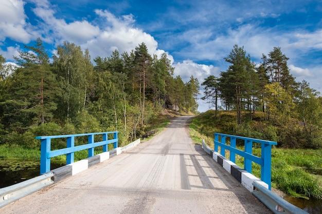 Holzbrücke und eine straße zum dorf soskua in karelien in nordrussland
