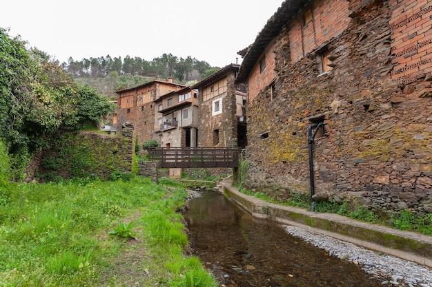 Holzbrücke zur überquerung des arrago-flusses vor dem hintergrund traditioneller schiefer- und lehmhäuser