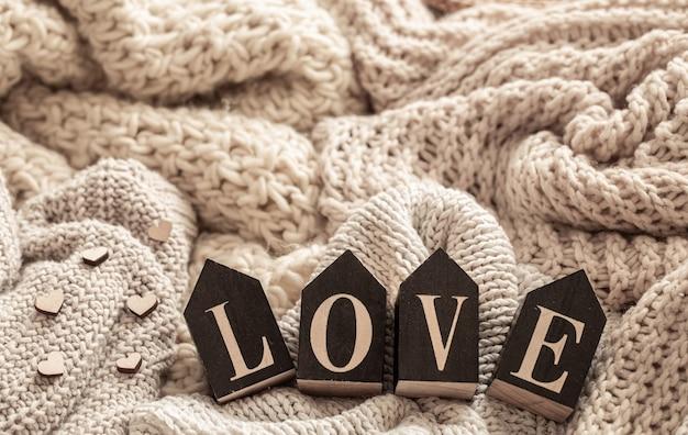 Holzbuchstaben bilden das wort liebe auf einem hintergrund von kuscheligen strickwaren. valentinstag urlaubskonzept.