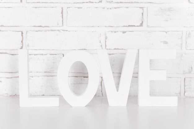 Holzbuchstaben liebe über weiße mauer
