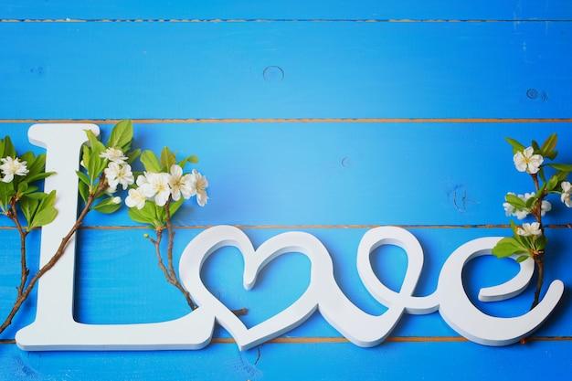 Holzbuchstaben lieben mit den zweigen der kirschblüten auf einem alten hölzernen hintergrund