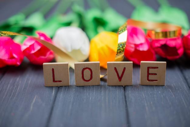 Holzbuchstaben schriftzug text liebe mit roten blumen für eine feiertagshochzeit valentinstag