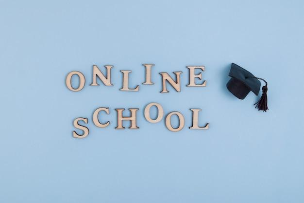 Holzbuchstaben schule online und absolventenmütze auf blauer oberfläche