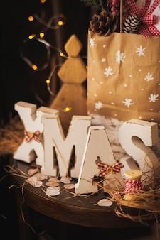 Holzbuchstaben weihnachten auf alten vintage stuhl mit paket von geschenken