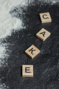Holzbuchstaben wie kuchen auf schwarz geschrieben.