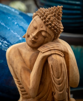 Holzbuddha mit kopf auf händen