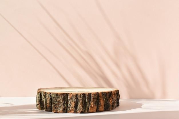 Holzbühne mit schatten zur präsentation auf beigem hintergrund.
