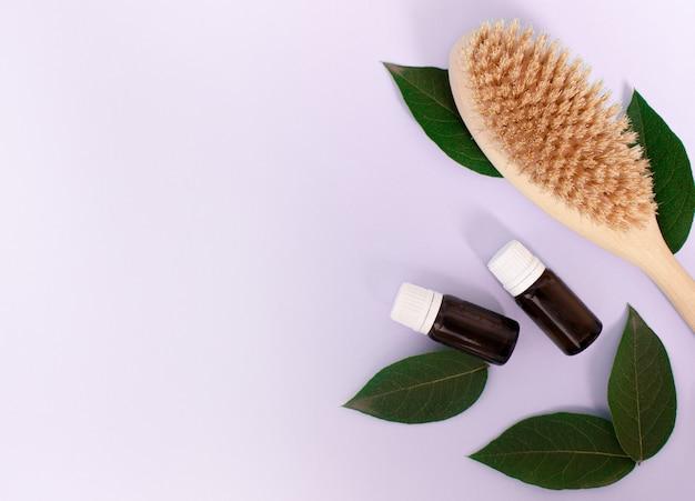 Holzbürste für anticellulite-körpermassage und kosmetikflasche auf lila hellem hintergrund körperpflege...