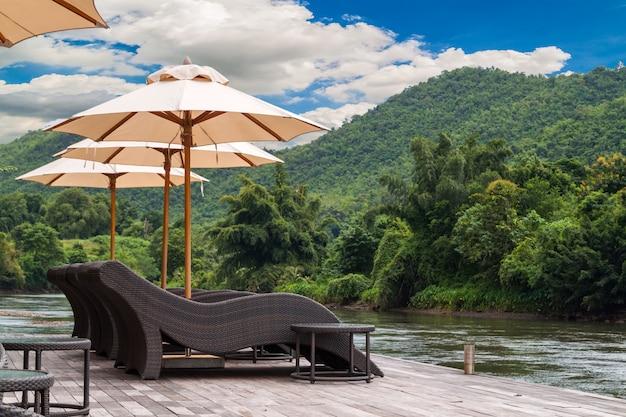 Holzdeck mit dem weben des weichen weißen regenschirms neben fluss in thailand
