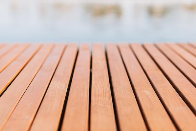 Holzdielenboden auf dem hintergrund eines teiches