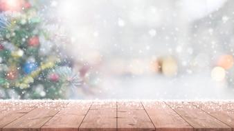 Hölzerne Tischplatte auf Unschärfe mit bokeh Weihnachtsbaumhintergrund mit Schneefällen