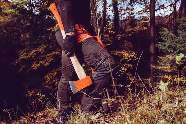 Holzfäller mit axt und kettensäge