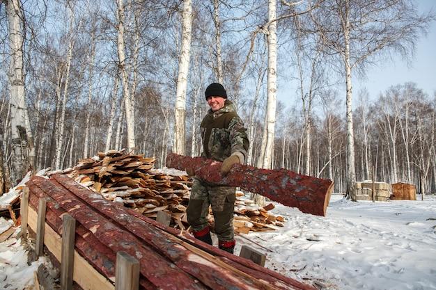 Holzfäller sägt im winter einen baum im wald, russland für brennholz