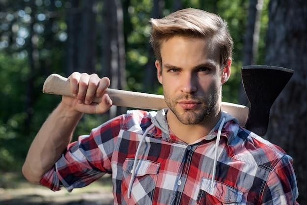 Holzfäller schöner mann auf ernstem gesicht mit axt im freien