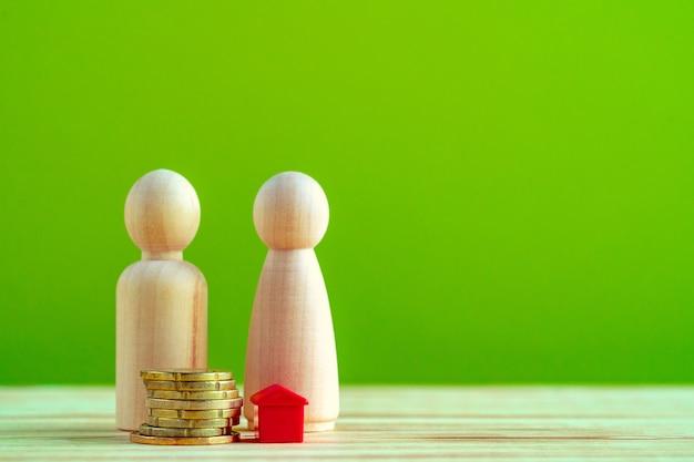 Holzfamilie mit spielzeughaus und stapel münzen. einsparungen für hauskaufkonzept