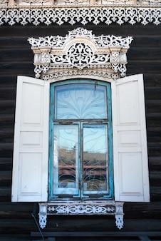 Holzfenster mit fensterläden und geschnitzten mustern an den fenstern in einem rustikalen alten haus