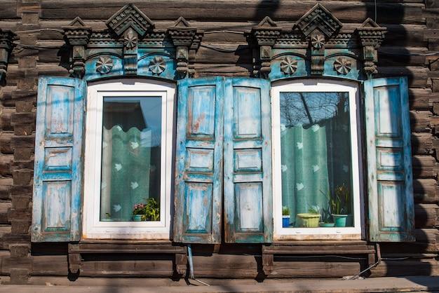 Holzfenster mit fensterläden und geschnitzten mustern an den fenstern in einem rustikalen holzhaus