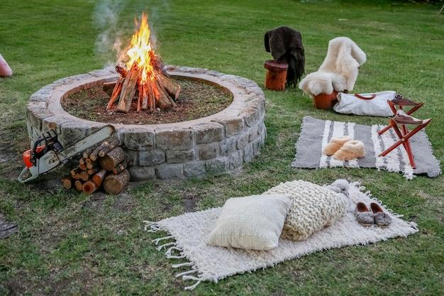 Holzfeuer mit bänken im garten bei sonnenuntergang