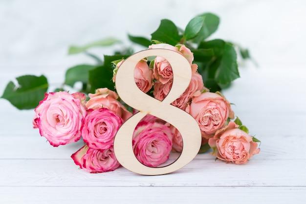 Holzfigur 8 mit rosa blumen auf einem weißen tisch. internationaler frauentag. 8. märz