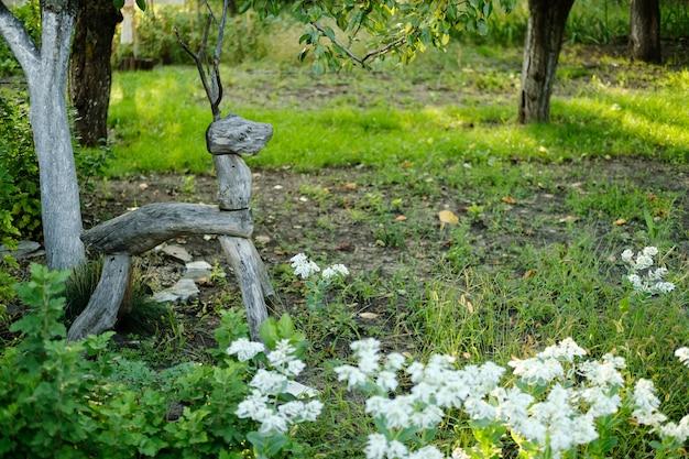 Holzfigur eines hirsches im garten sommer sonniger tag