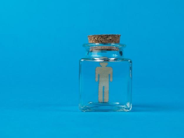 Holzfigur eines mannes in einer glasflasche auf blauem grund.