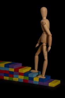 Holzfigur erklimmt eine holztreppe als symbol des beruflichen aufstiegs