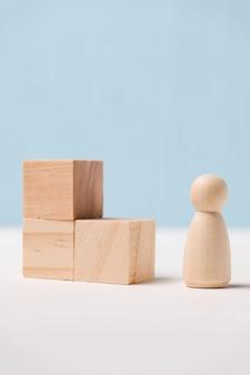 Holzfigur mit würfeln auf blauem grund. zielerreichungskonzept. weg zum erfolg. nahansicht.
