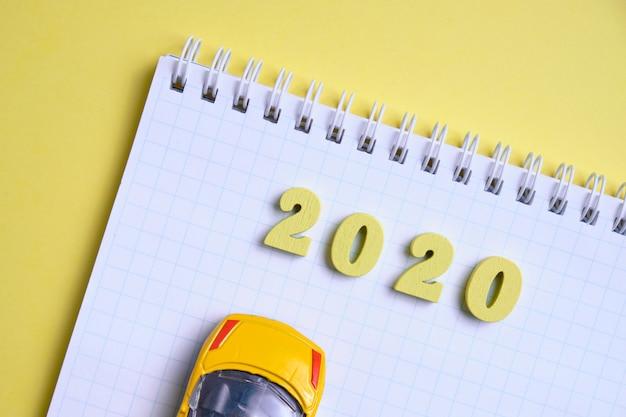 Holzfiguren 2020 auf einem notizblock mit einem spielzeugauto. das budgetkonzept im neuen jahr. draufsicht.