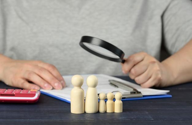 Holzfiguren der familie der kleinen männer auf der oberfläche eines mannes mit einer lupe, der die dokumente untersuchen wird