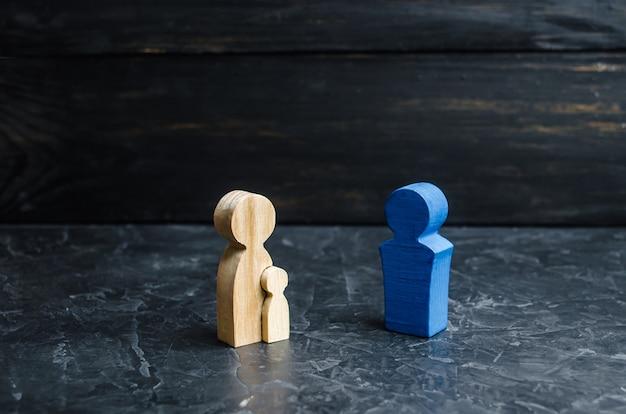 Holzfiguren der mutter mit kind und vater. das konzept einer starken familie, mäzenatentum.