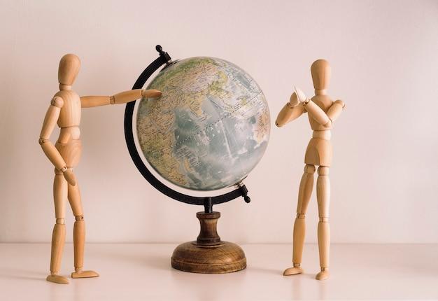 Holzfiguren, die reiseziel auf einer weltkarte wählen. reiselebensstil, glücksmomente