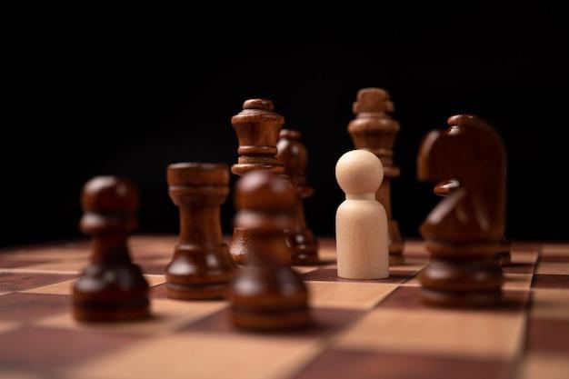 Holzfiguren (geschäftsmann) stehen dem schachkönig gegenüber und befinden sich im schachkreis.