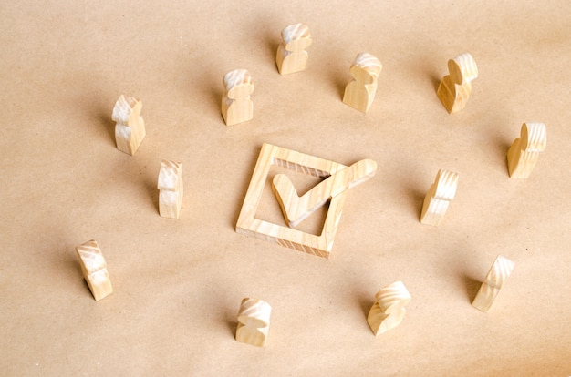 Holzfiguren umgeben die checkbox mit einem häkchen. das konzept der wahlen