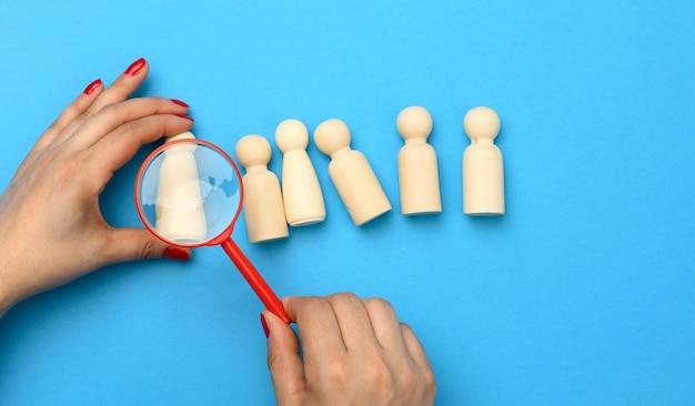 Holzfiguren von männern auf blauem grund und einer roten lupe. rekrutierungskonzept, suche nach talentierten und fähigen mitarbeitern, karriereentwicklung