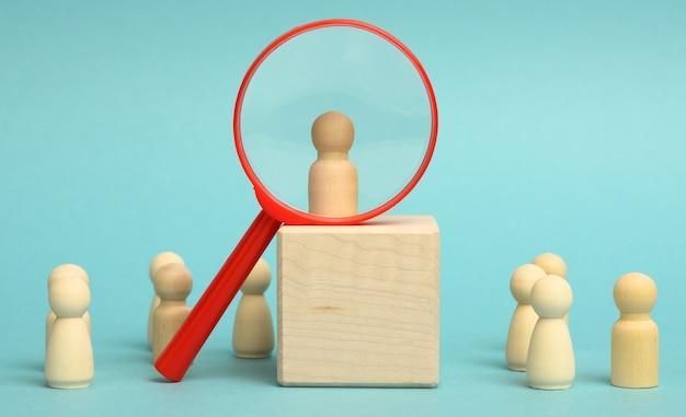 Holzfiguren von männern stehen auf einem beigen hintergrund und einer plastiklupe. rekrutierungskonzept, suche nach talentierten und fähigen mitarbeitern, karriereentwicklung